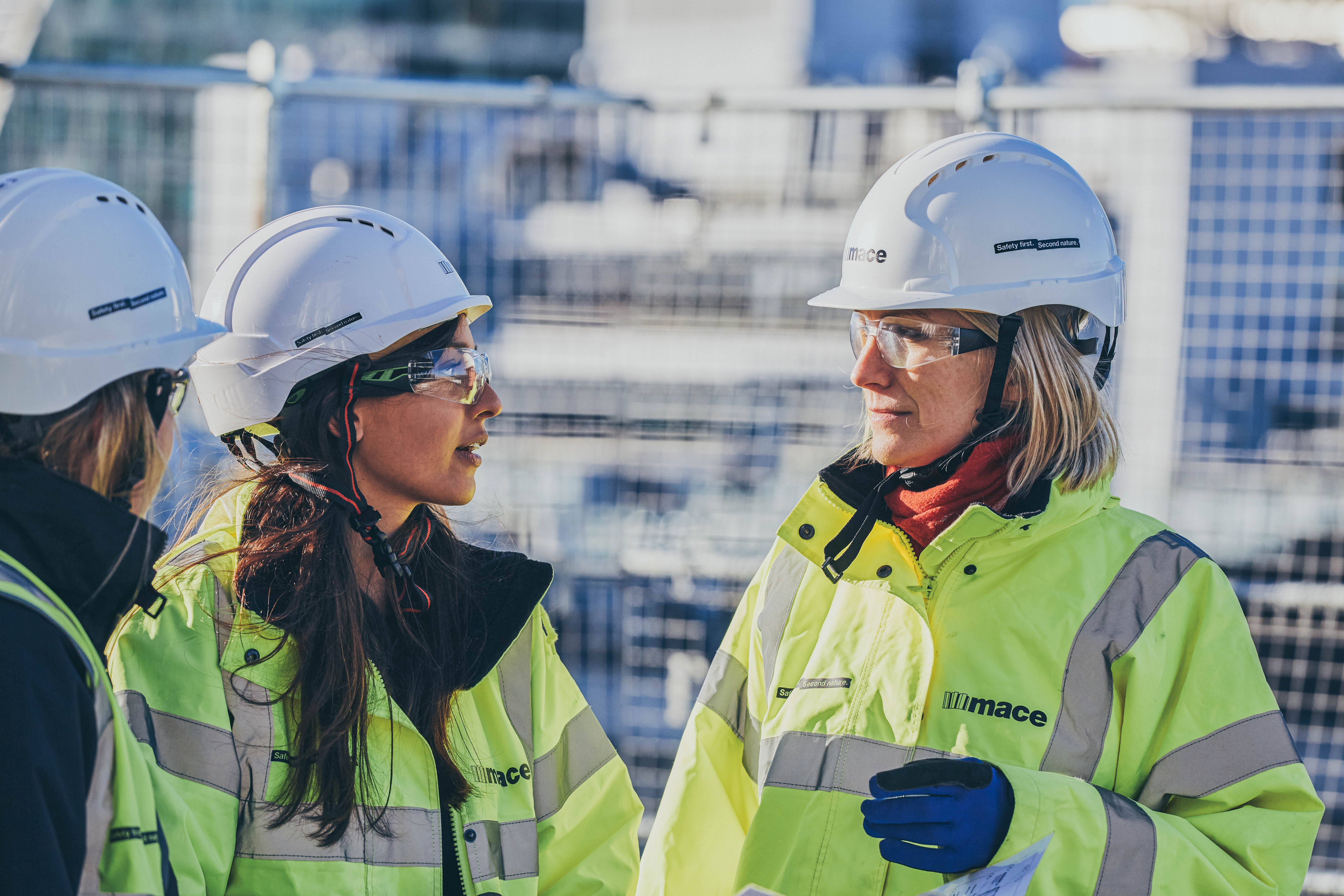 Two women in hivis jackets on a construction site in the daytime