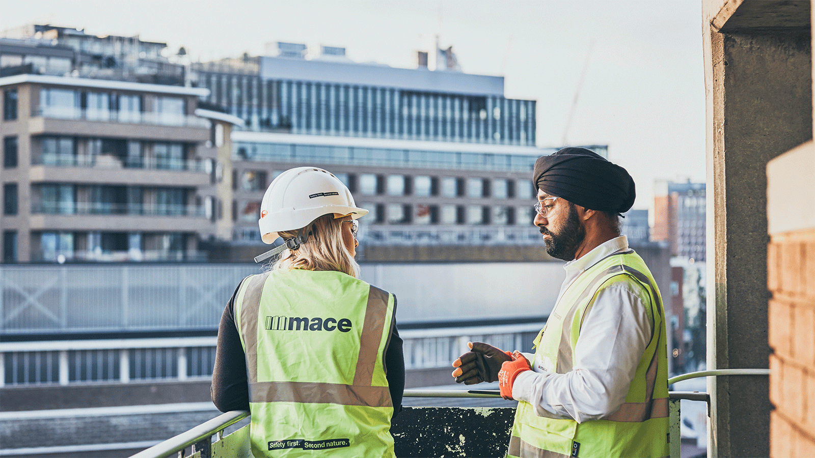 A man and a women wearing hivis jackets looking over at buildings on a  balcony